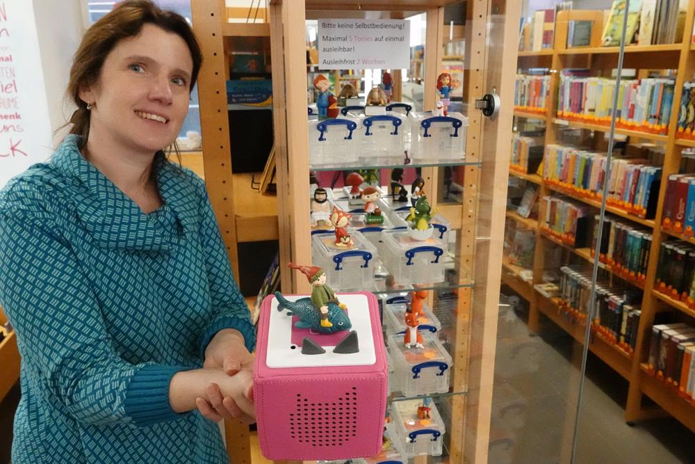 Diana Lange mit einer Tonie-Box und einer Vitrine mit verschiedenen Figuren. Diese können in der Stadtbücherei ausgeliehen werden (Foto: Stadt Rottweil)