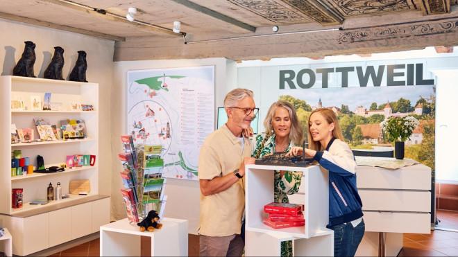 Innenbereich der Tourist-Information. Mitarbeiterin zeigt Gästen die verschiedenen Türme der Stadt mit Hilfe eines Reliefs.